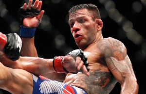 Rafael dos Anjos, right, delivers a kick to Anthony Pettis during a men's lightweight mixed martial arts title bout, Saturday night, March 14, 2015, at UFC 185 in Dallas. Rafael dos Anjos won in five rounds. (AP Photo/Brandon Wade) ORG XMIT: DNA143